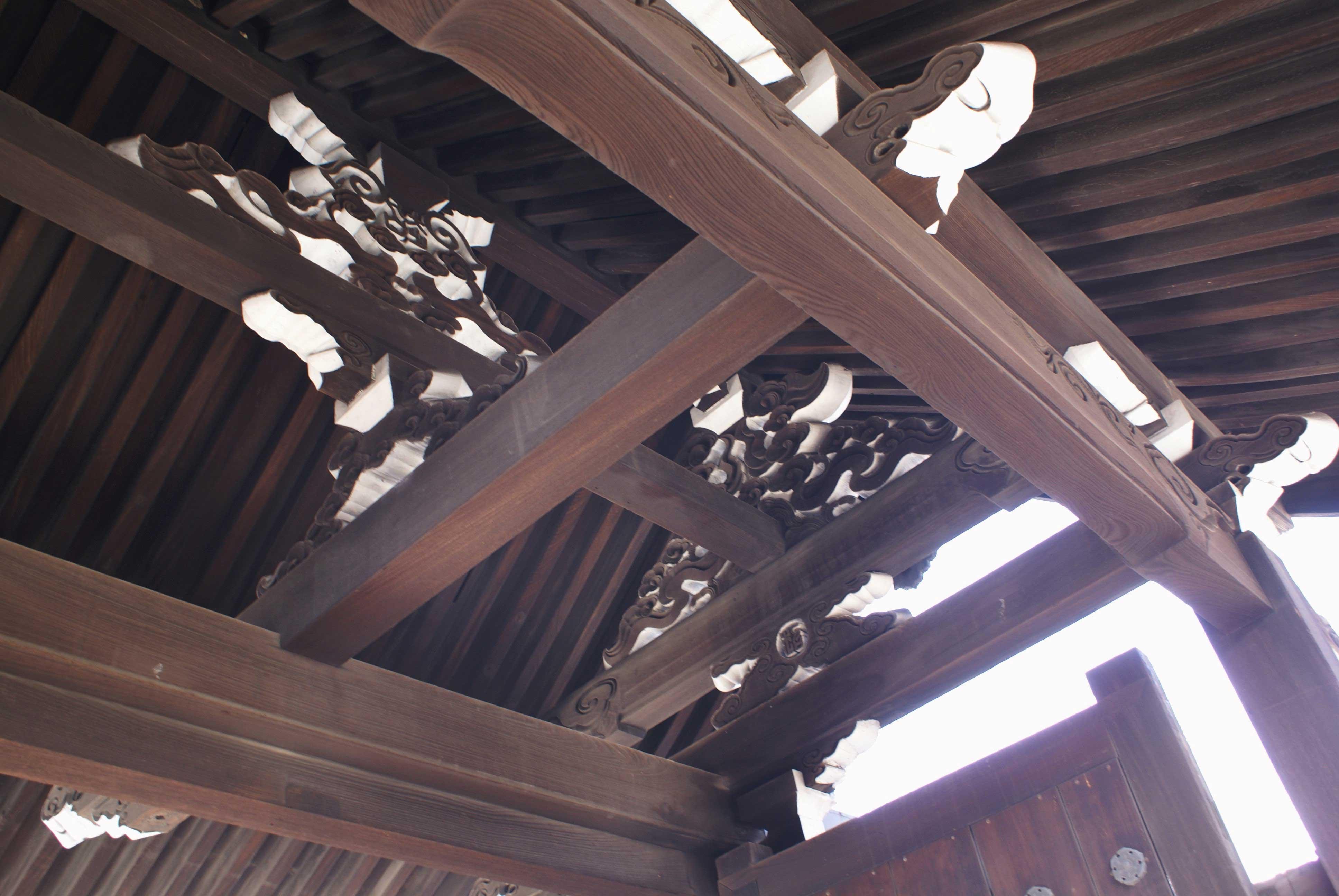 <p>控柱側からの見上げ</p>妻や中備は流水や雲紋風に彫られた蟇股とする。木材本来の色と小口塗装のコントラストが美しい。