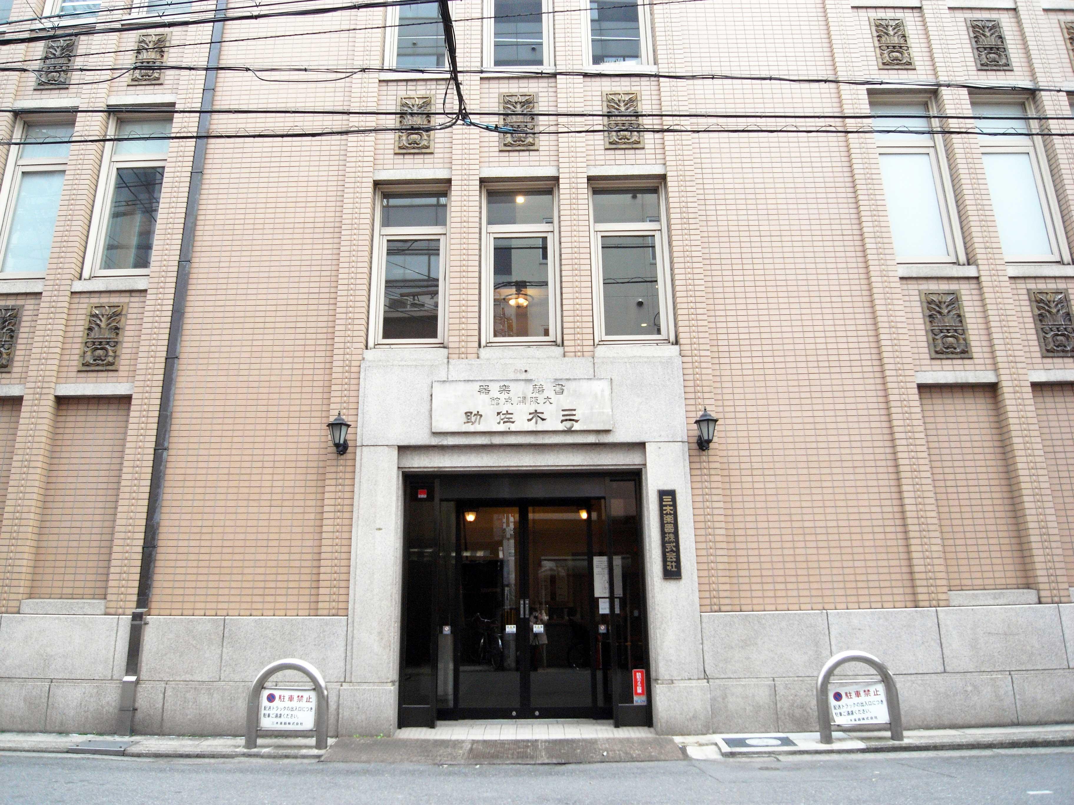 <p>北側事務所入口</p>従入口大理石的銘板上可得知,建築物竣工時是経営書籍業和楽器店的「三木佐助商店」。