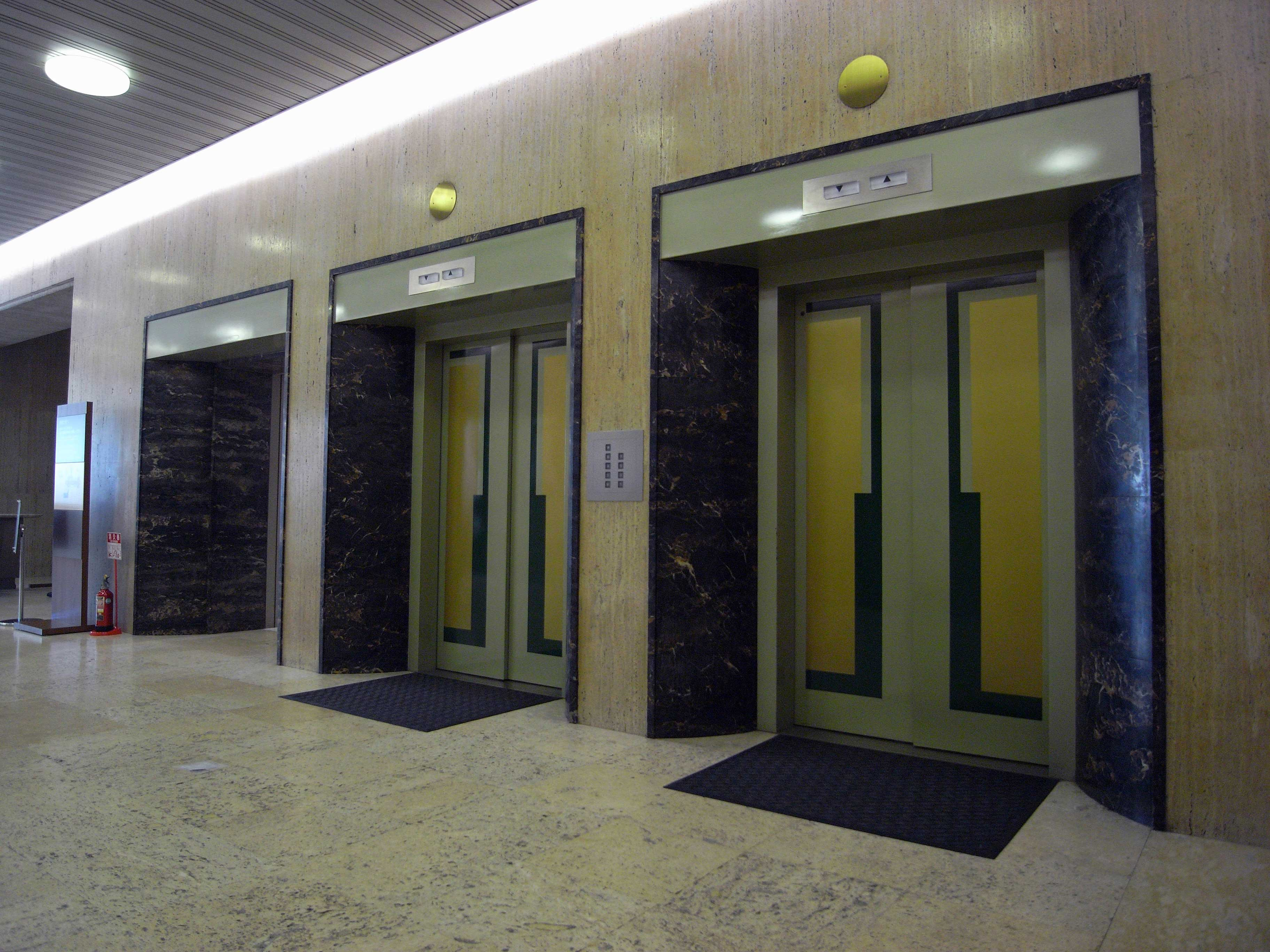 <p>1階エレベーターホール</p>床は琉球産トラバーチン(大理石)、壁はイタリア産のトラバーチンが貼られ、竣工当時の面影を残している。
