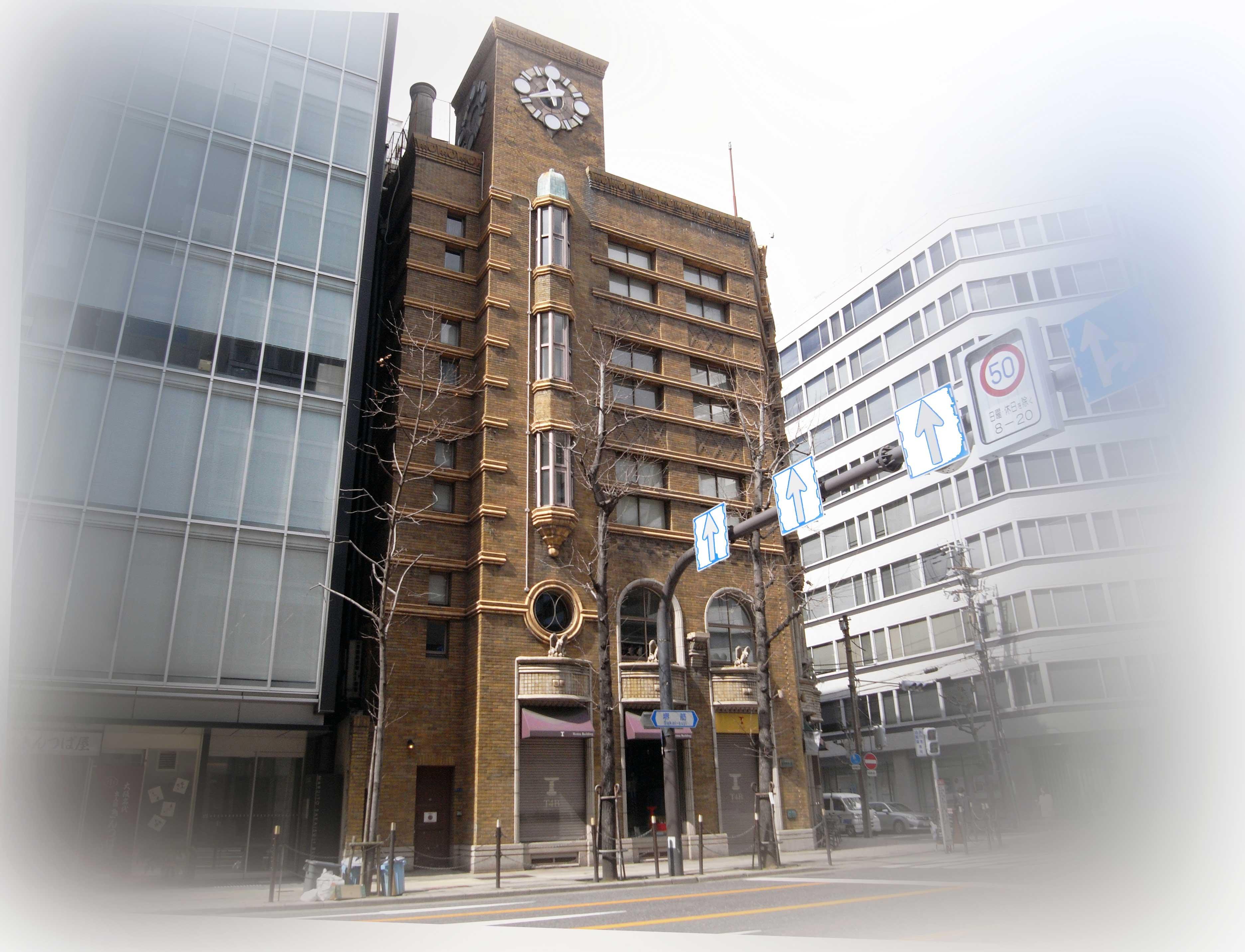 <p>堺筋側東面外観</p>時計塔まで伸びるファサード。5階から3階にかけての縦長出窓と2階部分の丸窓は時計の振り子をデザインしたもの。