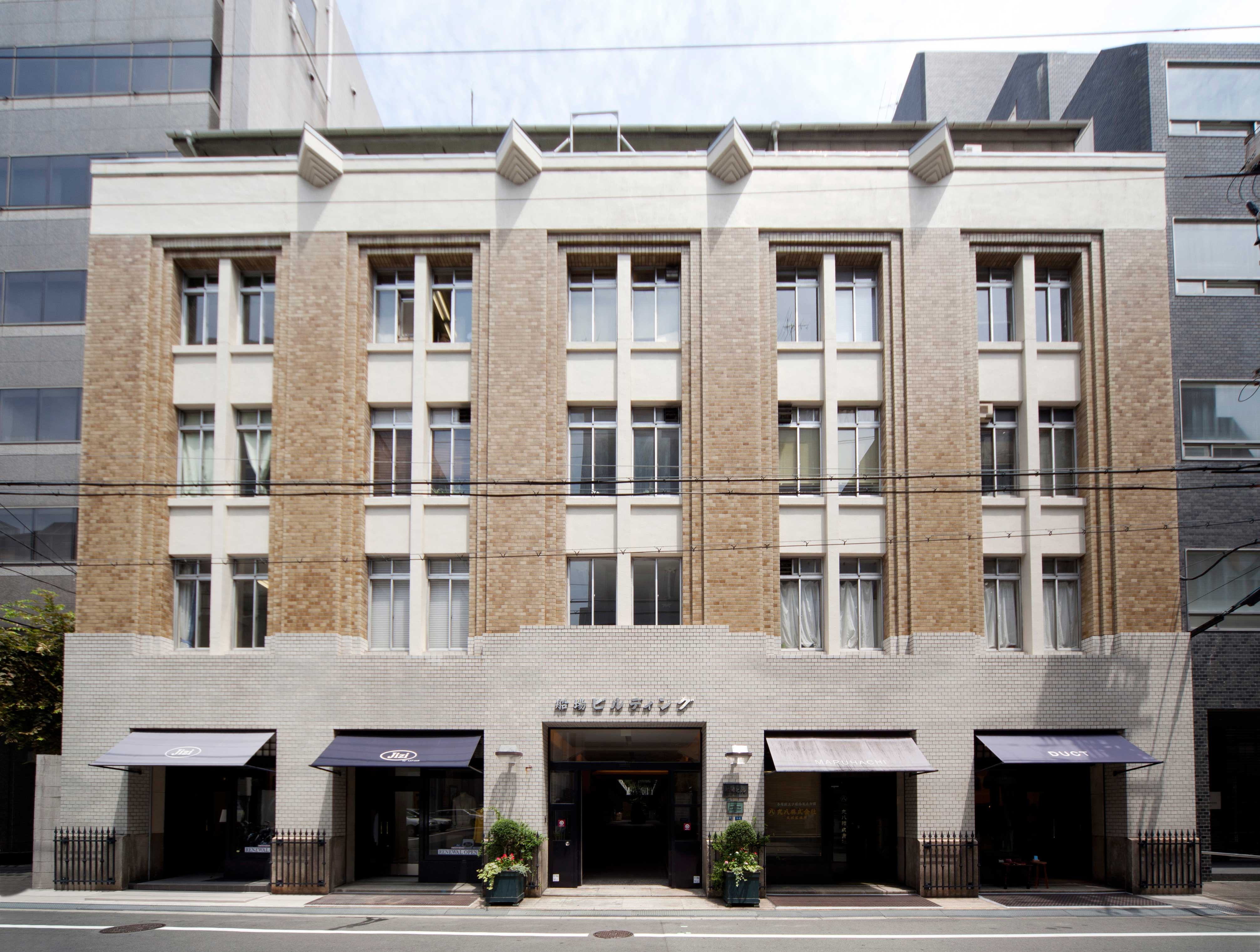 <p>南面正面外観</p>柱型を出して縦線が強調された外観デザインは、1階は白色の2階より上階は茶色の小口タイルを張ってコントラストをはっきりさせている。