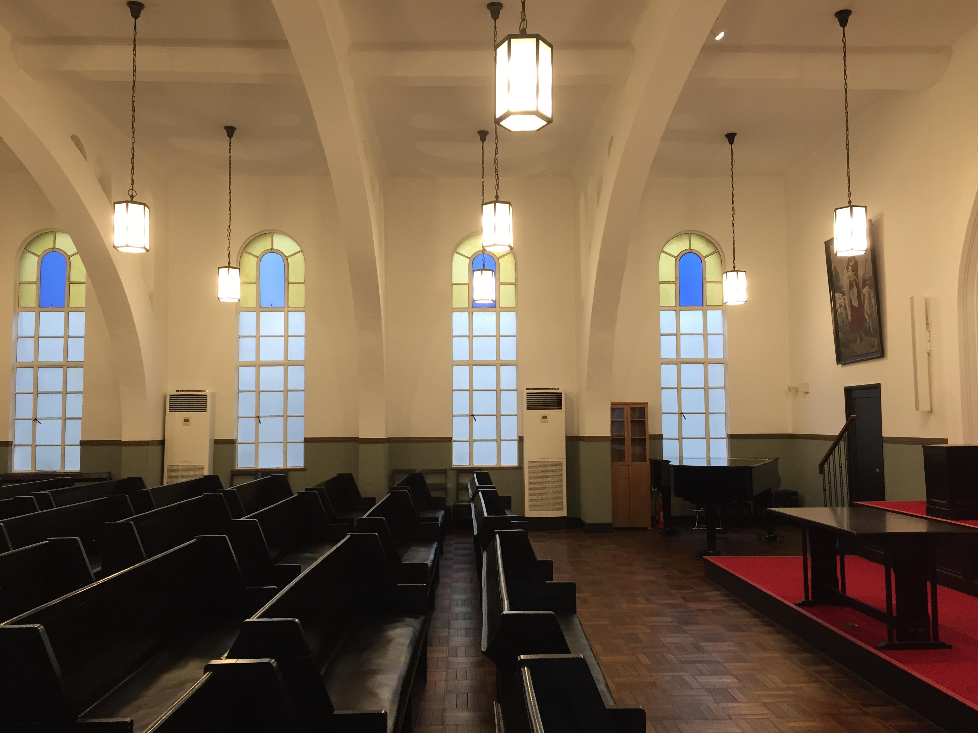 <p>2階礼拝堂2</p>祭壇と座席との関係を横の座席通路から見る。天井の白と長椅子とフローリングの濃い茶色のコントラストをきかせたデザインとなっている。