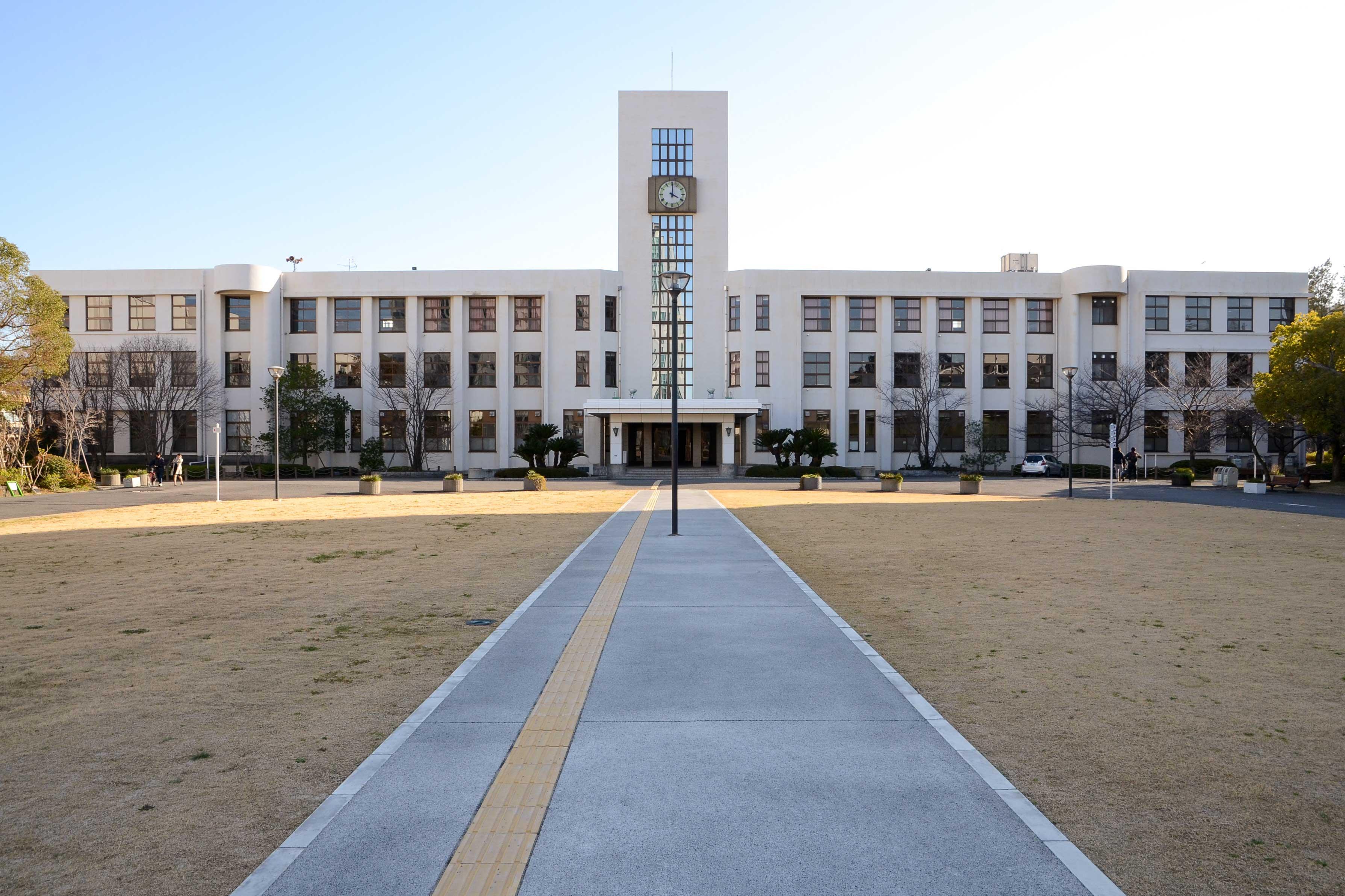 <p>全景(南面)</p>キャンパス正門に正面を向ける。塔を軸に左右対称の構成。両翼は途中で円筒形の突起で分節されている。