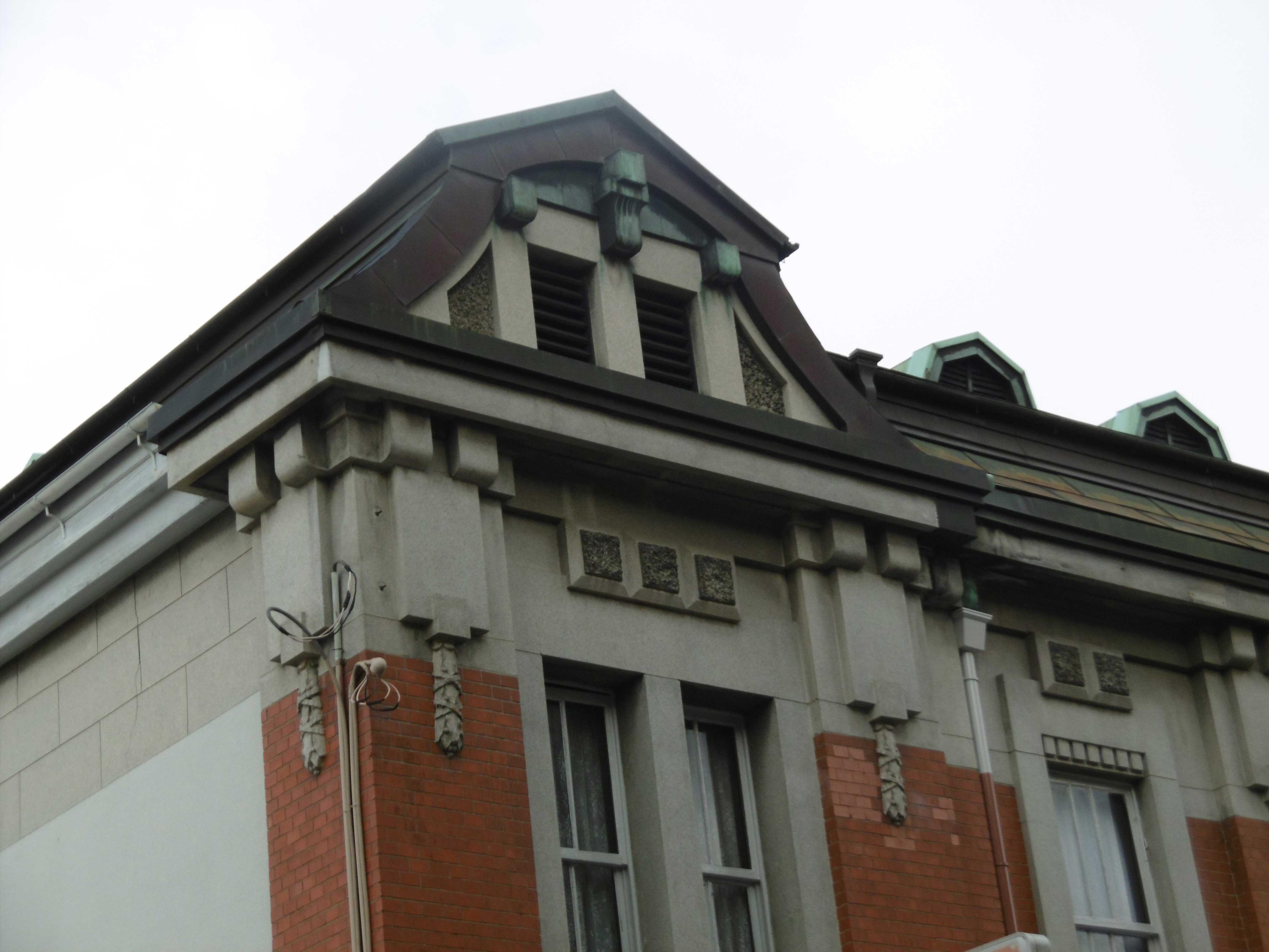 <p>正面西側のマンサード風屋根</p>西側部分は柱型、頂部コーニスのせり出し、特徴的な破風のマンサード風の妻面により、隅塔的な表情を出している。
