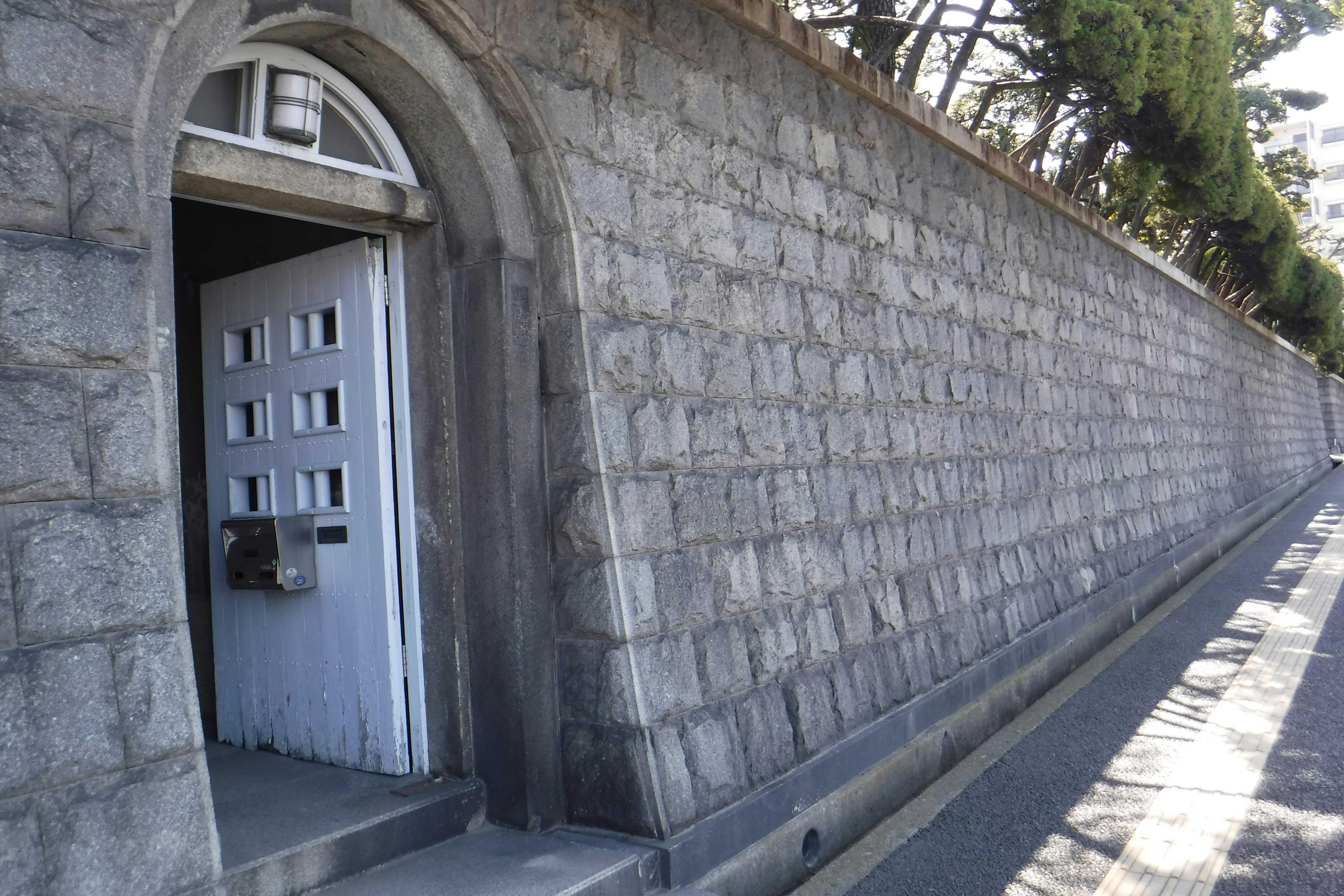 <p>石垣塀</p>こぶ出し仕上の花崗岩を布積とする。最高高さ3.4mを測り、北寄りに半円アーチの通用門を開く。