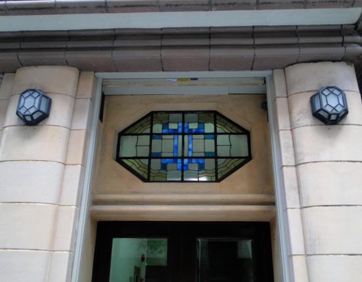 <p>通用口回りのデザイン(登録時)</p>八角形で左右対称のステンドグラス・玄関燈・扉把手。幾何学的でパターン化された模様がアールデコの特徴。