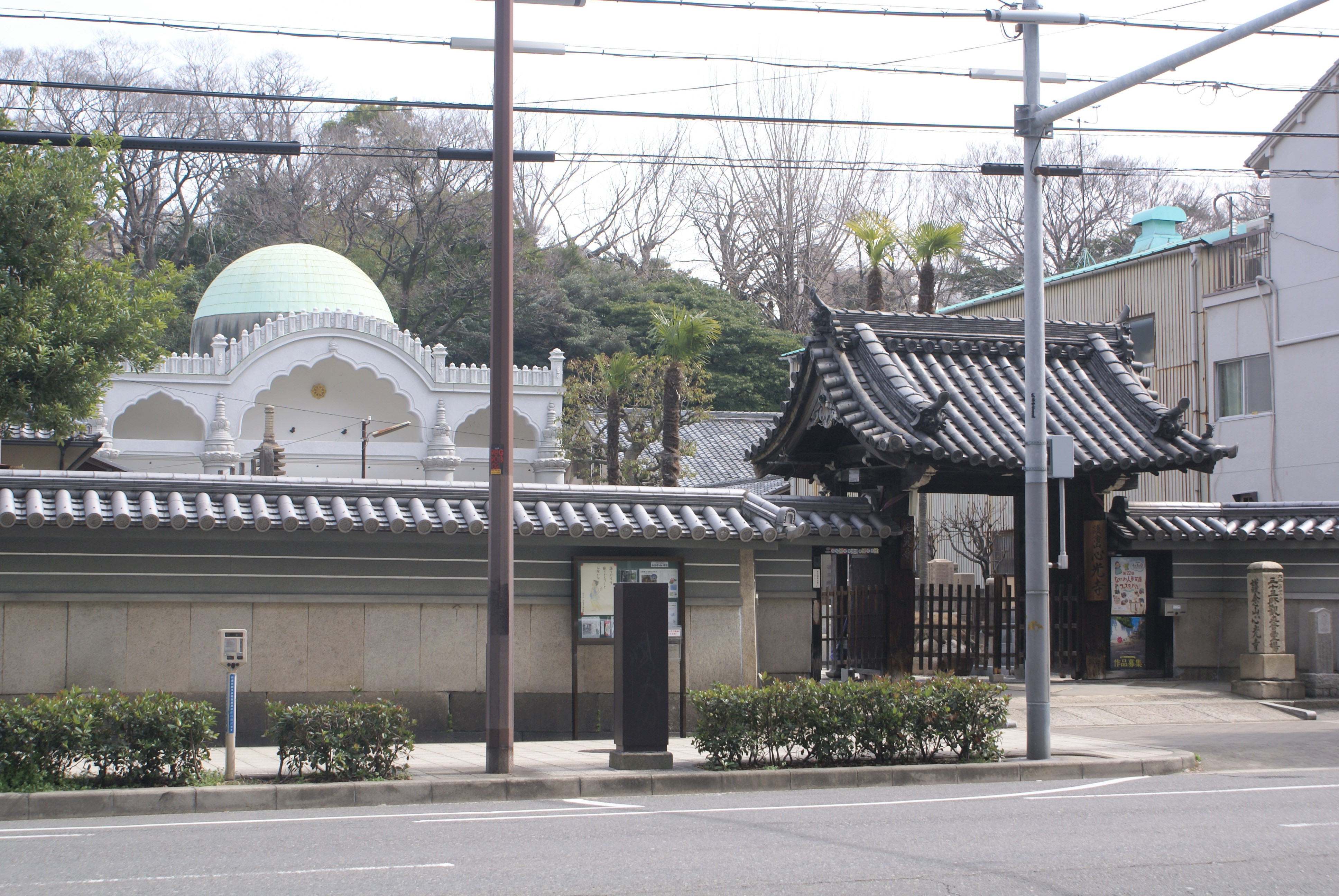 <p>心光寺山門と本堂</p>松屋町筋を挟んで山門とインド風の外観を持つ本堂を見る。松屋町筋に面するこの周辺の寺院は、本堂の前に墓地が広がり、横に庫裏という配置が多い。