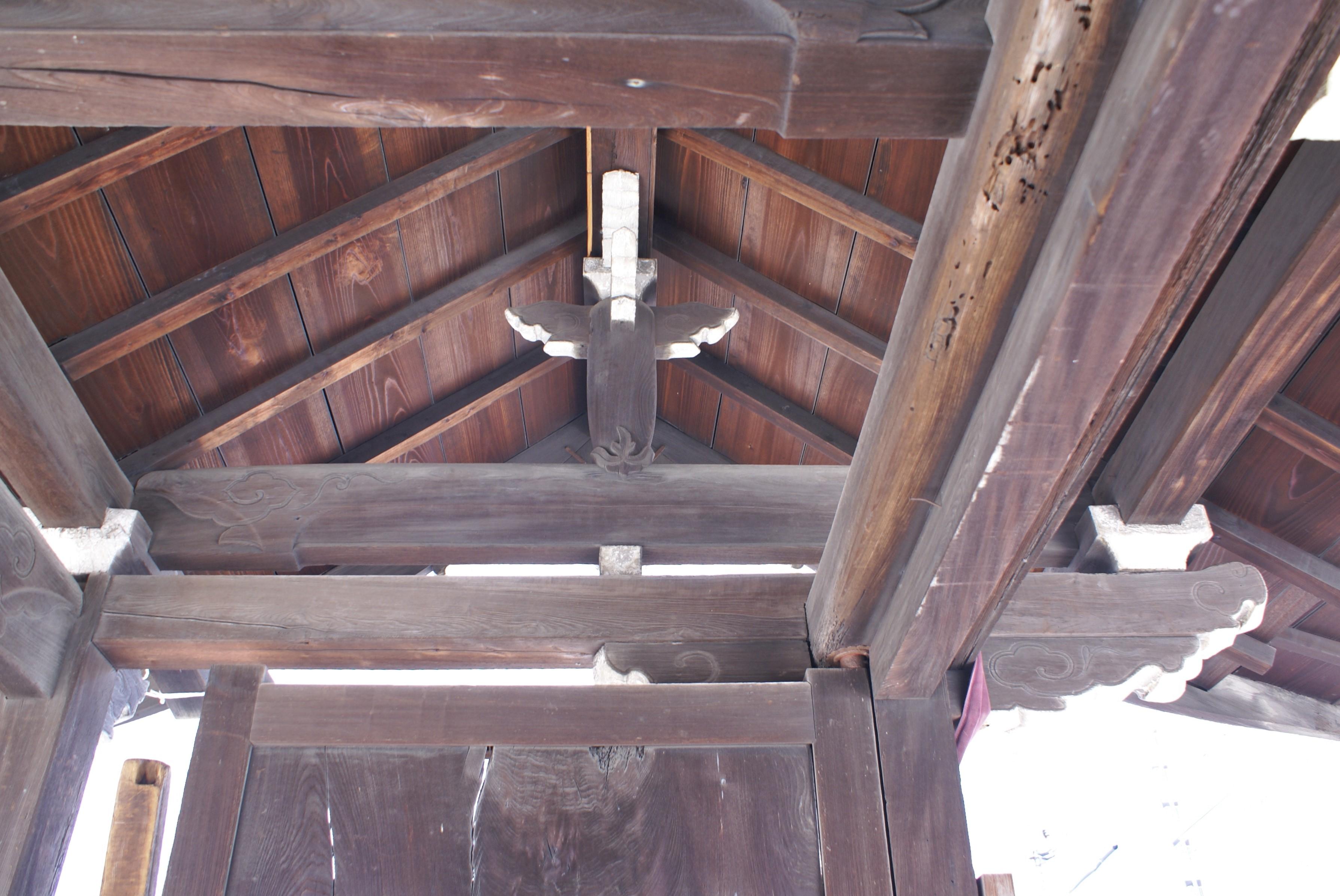 <p>山門中央からの見上げ</p>女梁・男梁・虹梁の彫刻と細かにデザインされた大瓶束と四方にでた木鼻が見える。