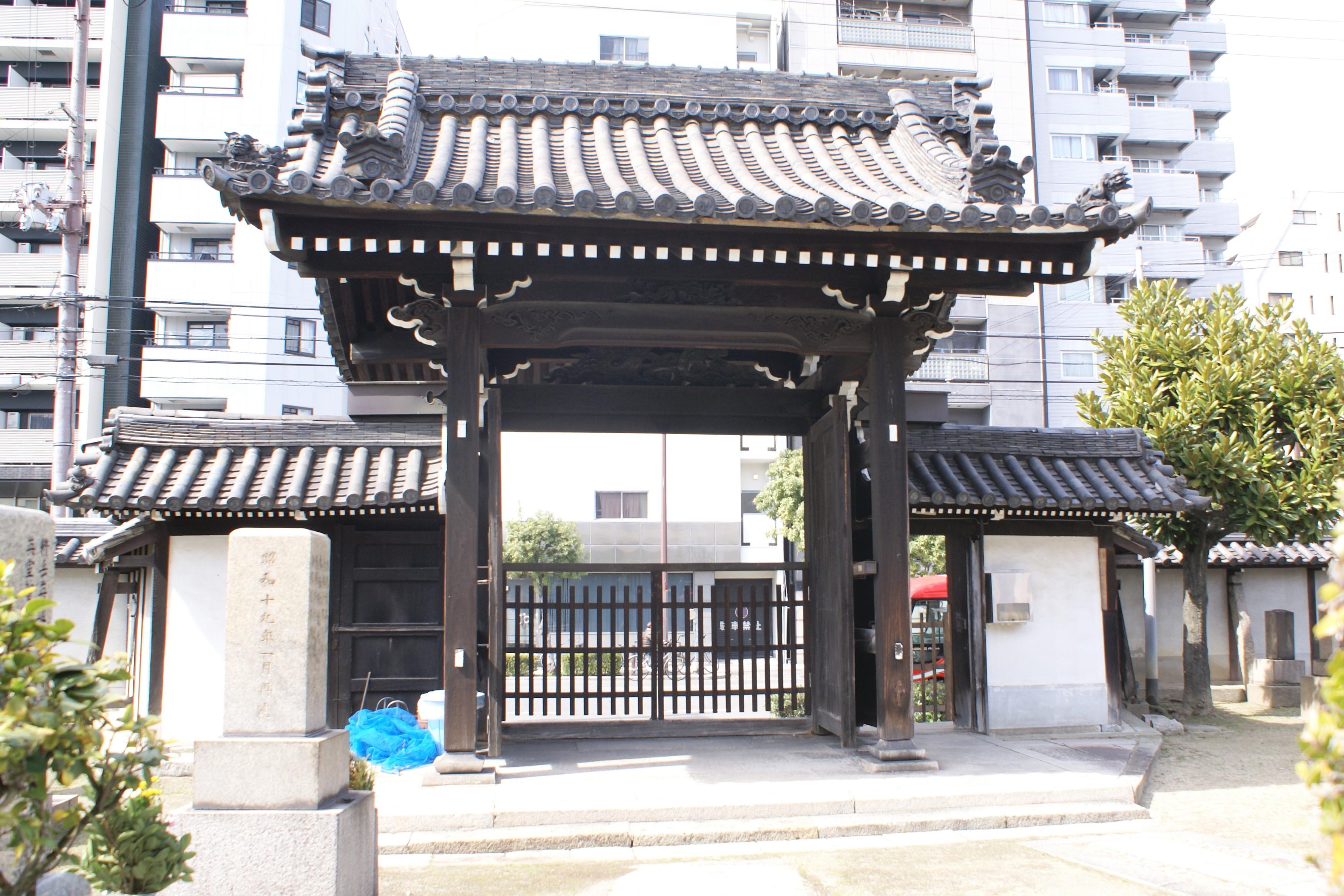 <p>境内内部から山門を見る。</p>各部位の彫刻、3か所の本瓦屋根の意匠の異なる飾り瓦や繁垂木が端正な美しさを醸しだしている。