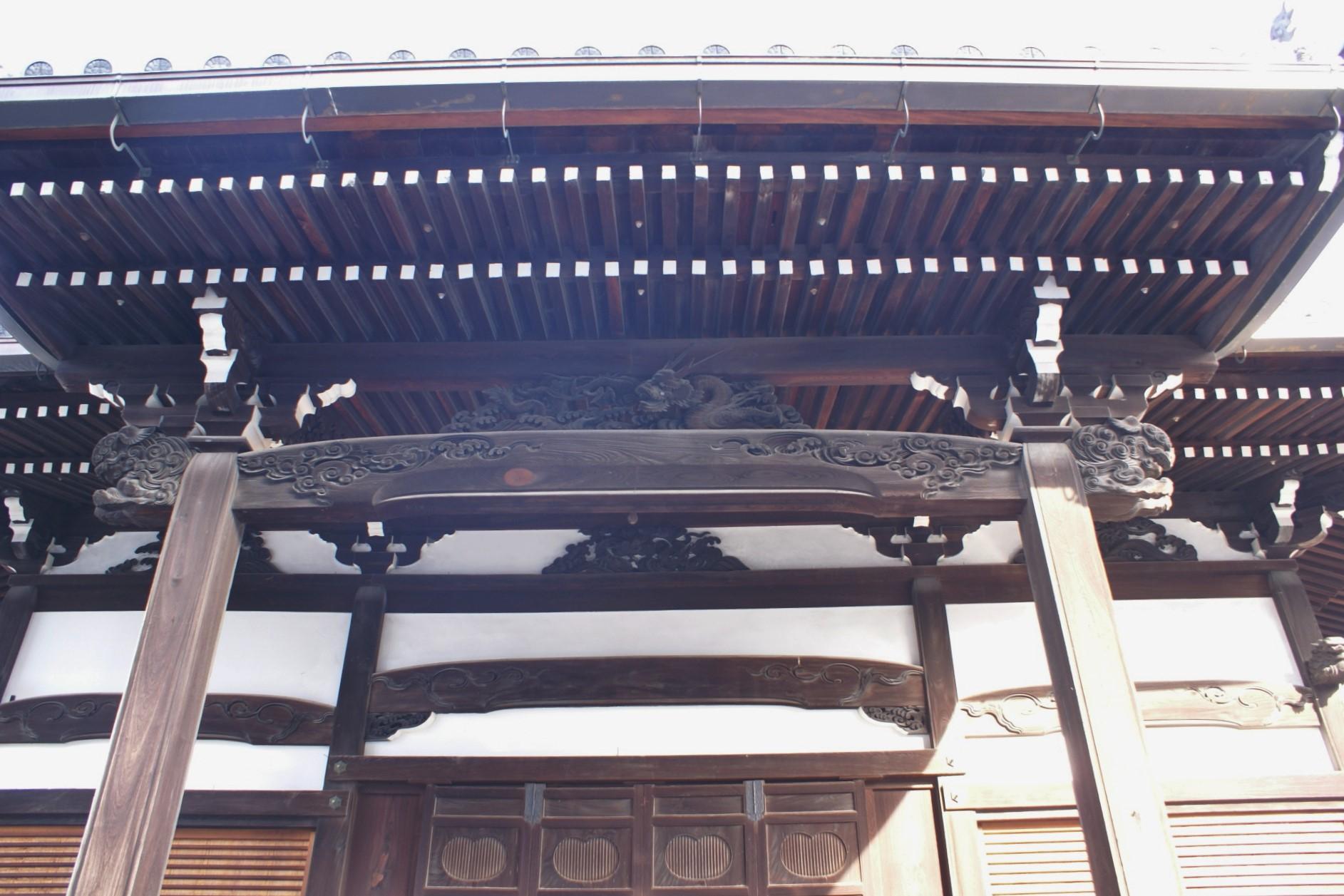 <p>向拝から本殿見上げ</p>頭貫とその上の中備の龍の彫刻、木鼻の獅子頭や建具など細部に丁寧な細工が施されている。また、2軒繁垂木となっている。