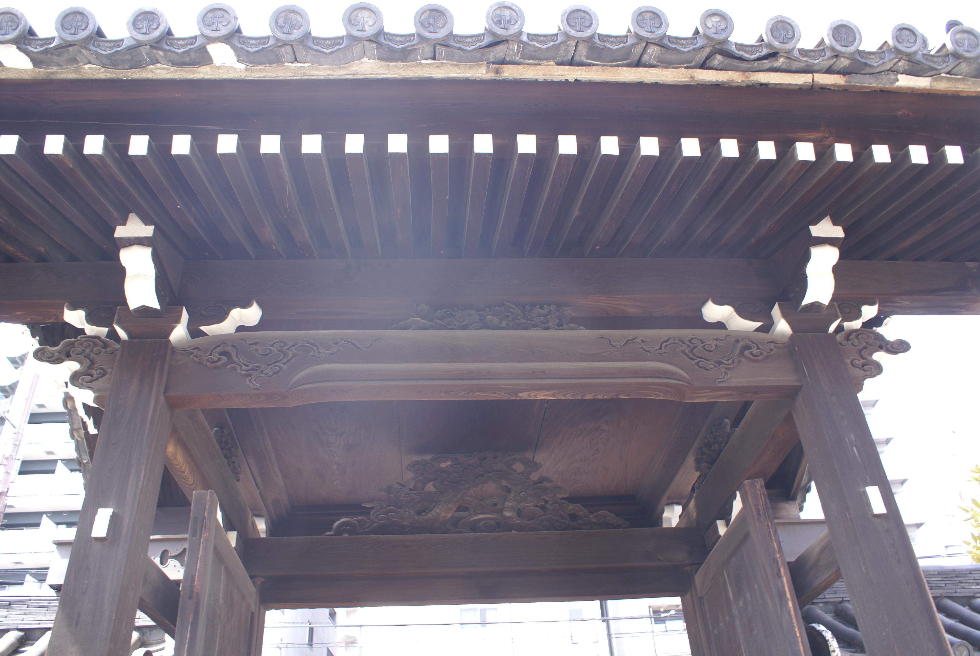 <p>境内内部からの山門見上げ。</p>中備の彫刻の背面と鏡天井が見える。