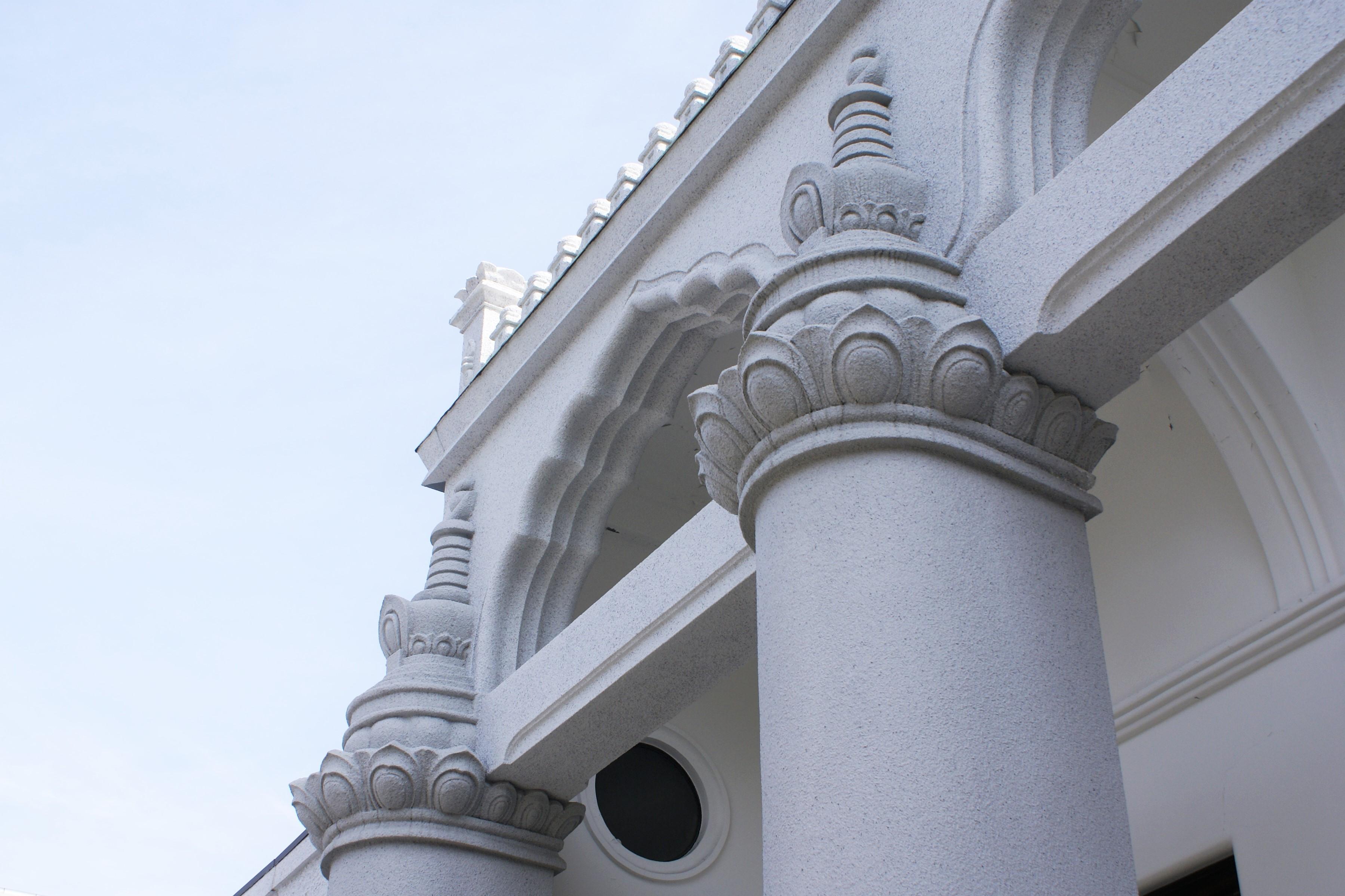 <p>本堂のディテール</p>柱上の相輪風の飾り,パラペットの宝珠柱風手摺子,多弁アーチなどによりインド風の外観となっている。