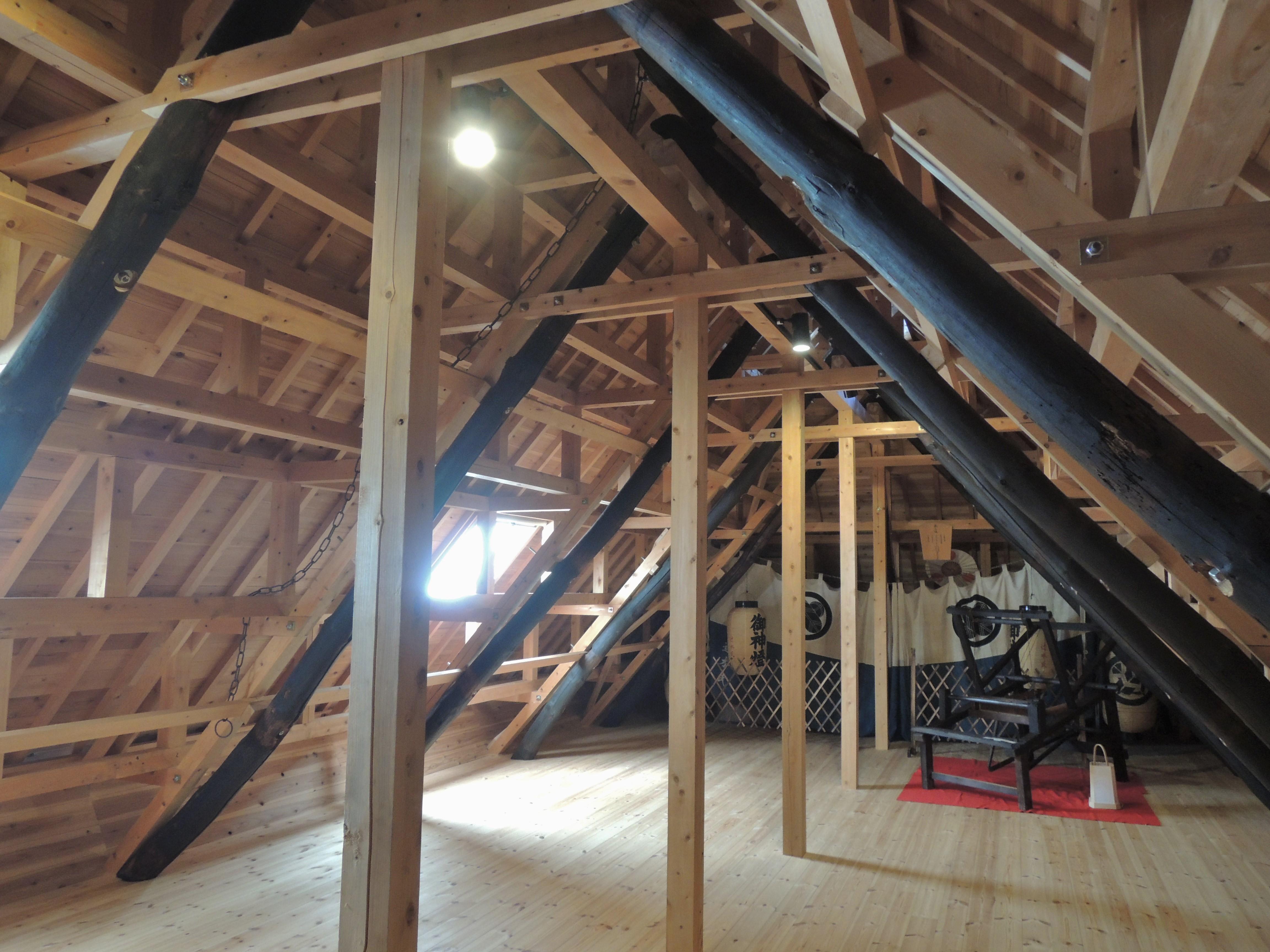 <p>屋根裏の構造</p>小屋組みを再構築し、棟木とサスを残す。垂木の位置は、元の茅葺きの厚み分を控えている。中央あたりに見える鉄の鎖は、茅を葺く時の命綱であった。床下には、断熱材として敷かれていた土をそのまま残して床板を貼っている。