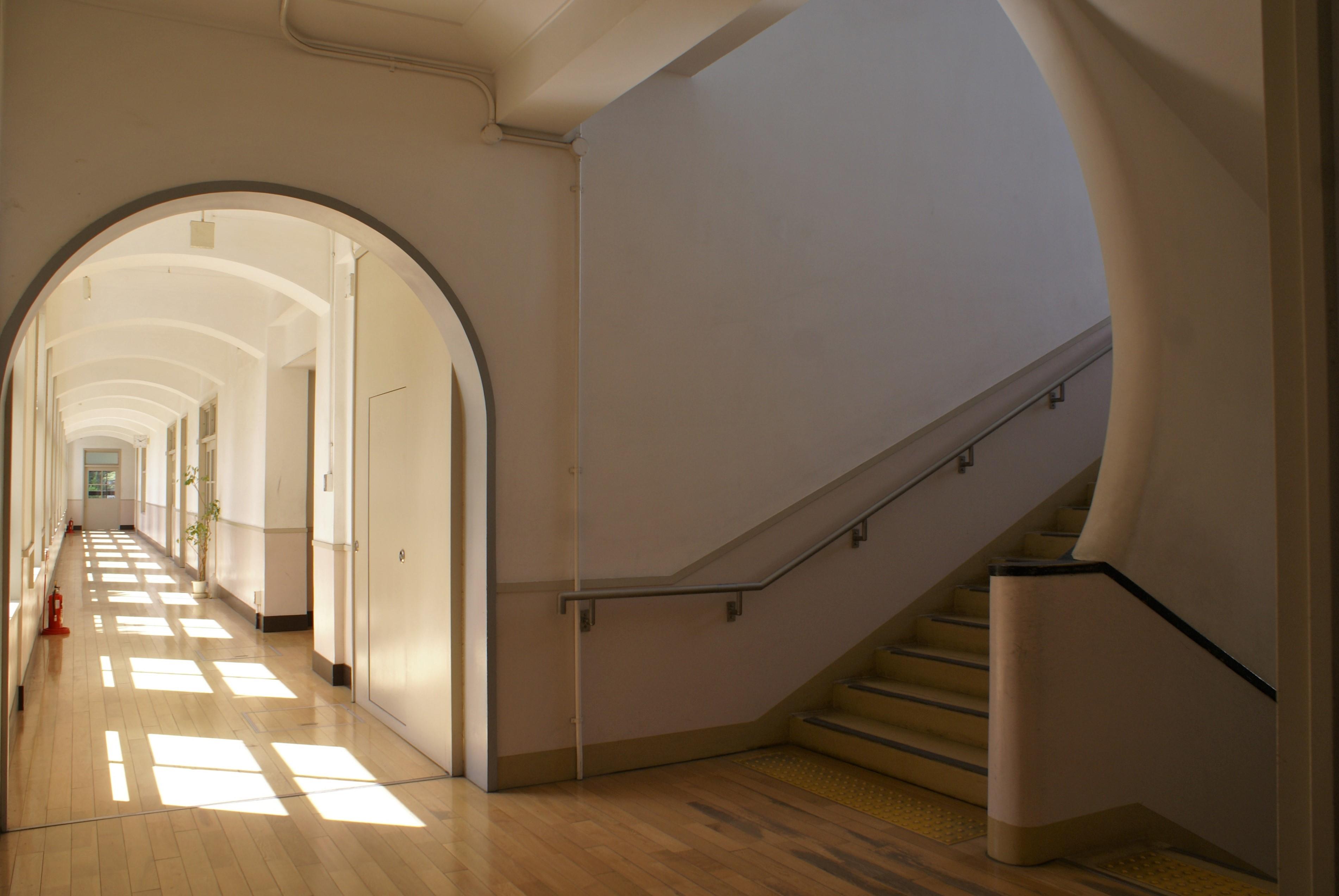 <p>北側東西棟から見る南北棟2E廊下</p>天井の梁や間仕切壁のアーチの形状とともに、階段の手摺壁や笠木部分にも曲線が用いられ、外部の直線的なイメージに対して、内部は優美さを感じさせる。階段から手前が一期工事部分である。平成の改修工事で、2階・3階の床が配線・配管のためかさ上げされたので、その分、建設当時よりも天井高さが低くなっている。<br />