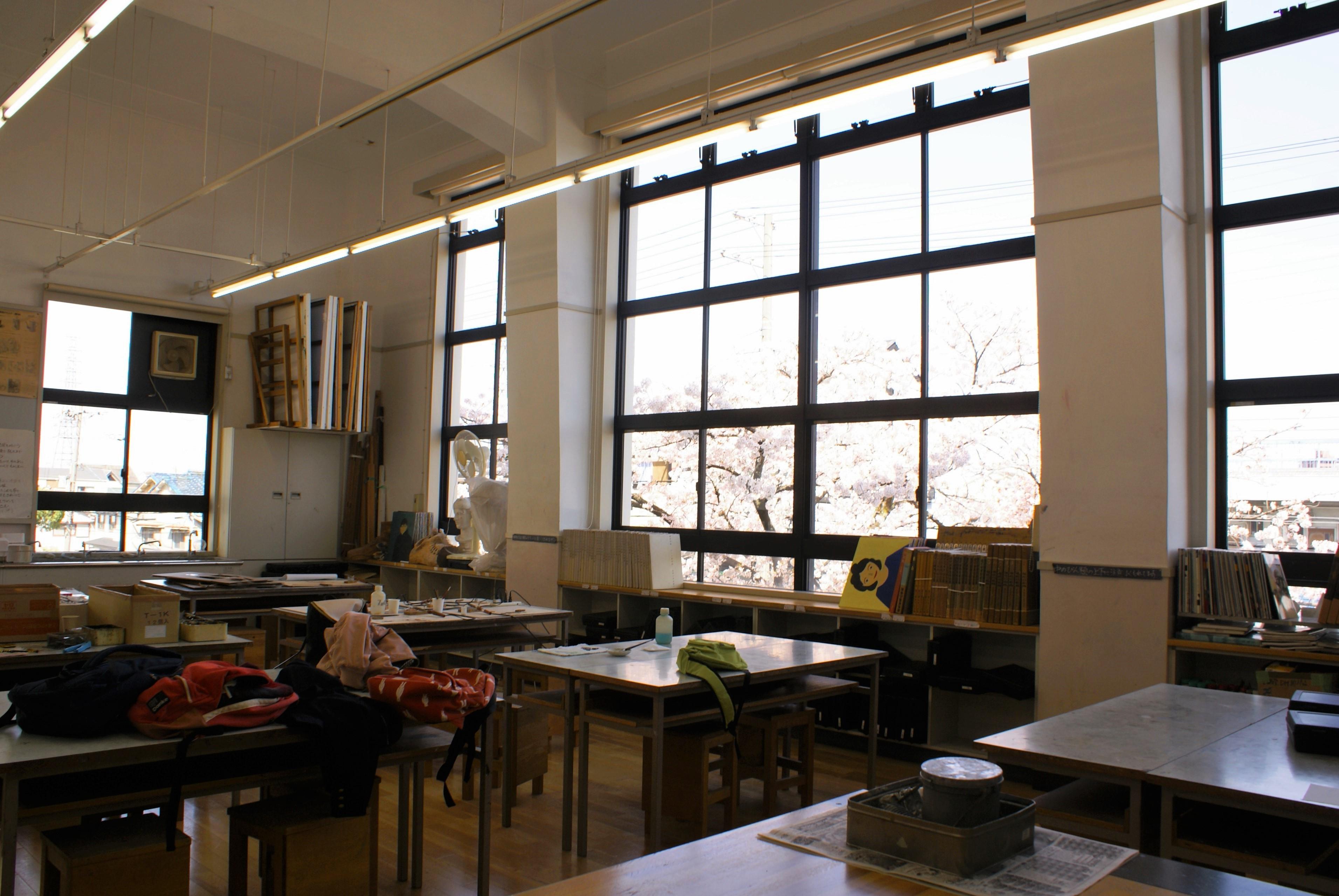 <p>吹抜天井の美術教室</p>一期工事で完成した美術教室は2階北西にあり、3階部分を吹抜天井としている。北側の開口を大きくとり、安定した光を取り入れている。美術アトリエを強く意識した設計であり、一部の専門課程を除いて、この空間の豊かさは当時ではほとんど例を見ないものだったと思われる。桜の時期は窓が花におおわれて美しい。