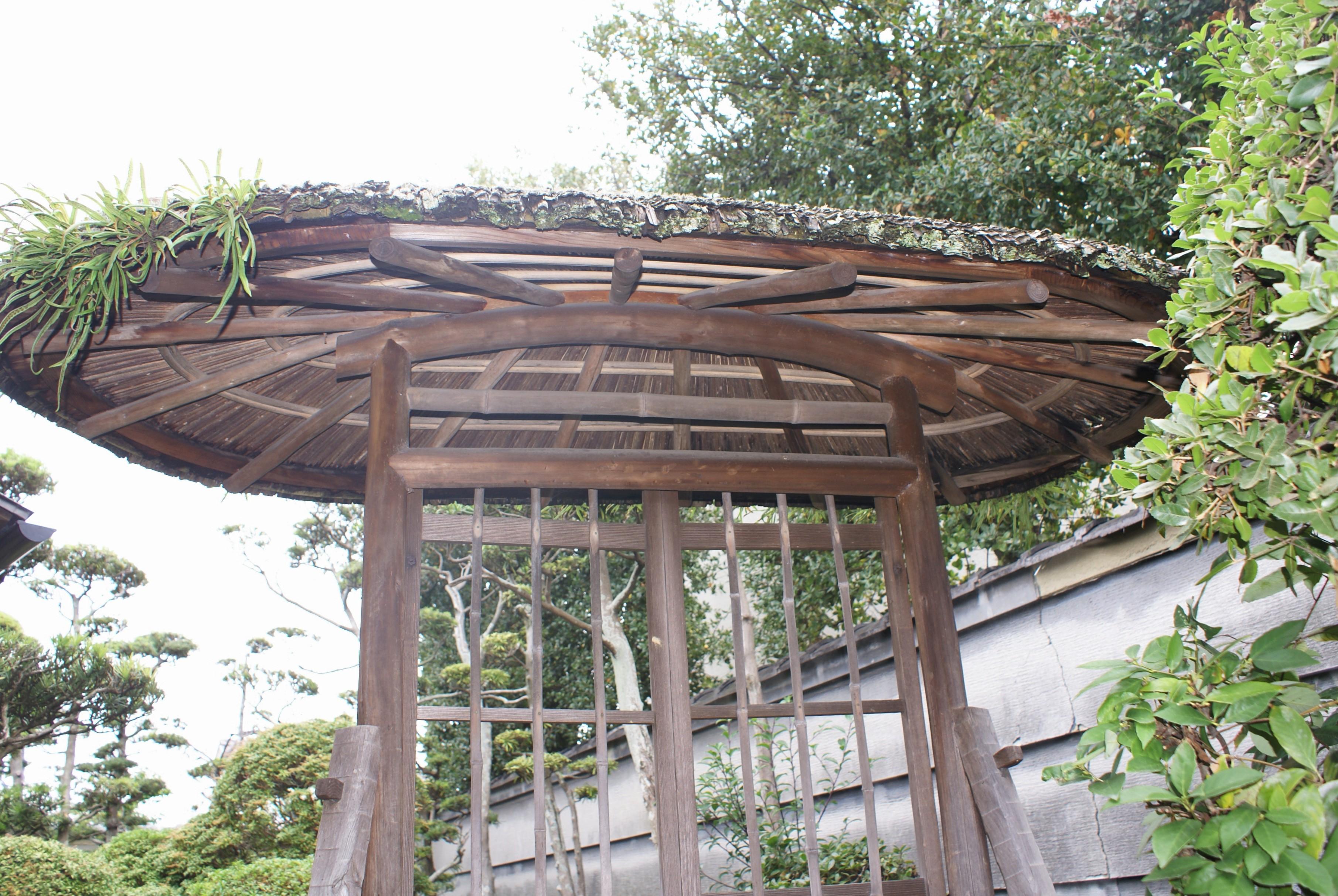 <p>編笠門見上げ</p>丸太柱に根曲りのナグリ材の控柱、竹簀戸を両開きに吊る。屋根は楕円平面で放射線状に丸太垂木が伸びる。