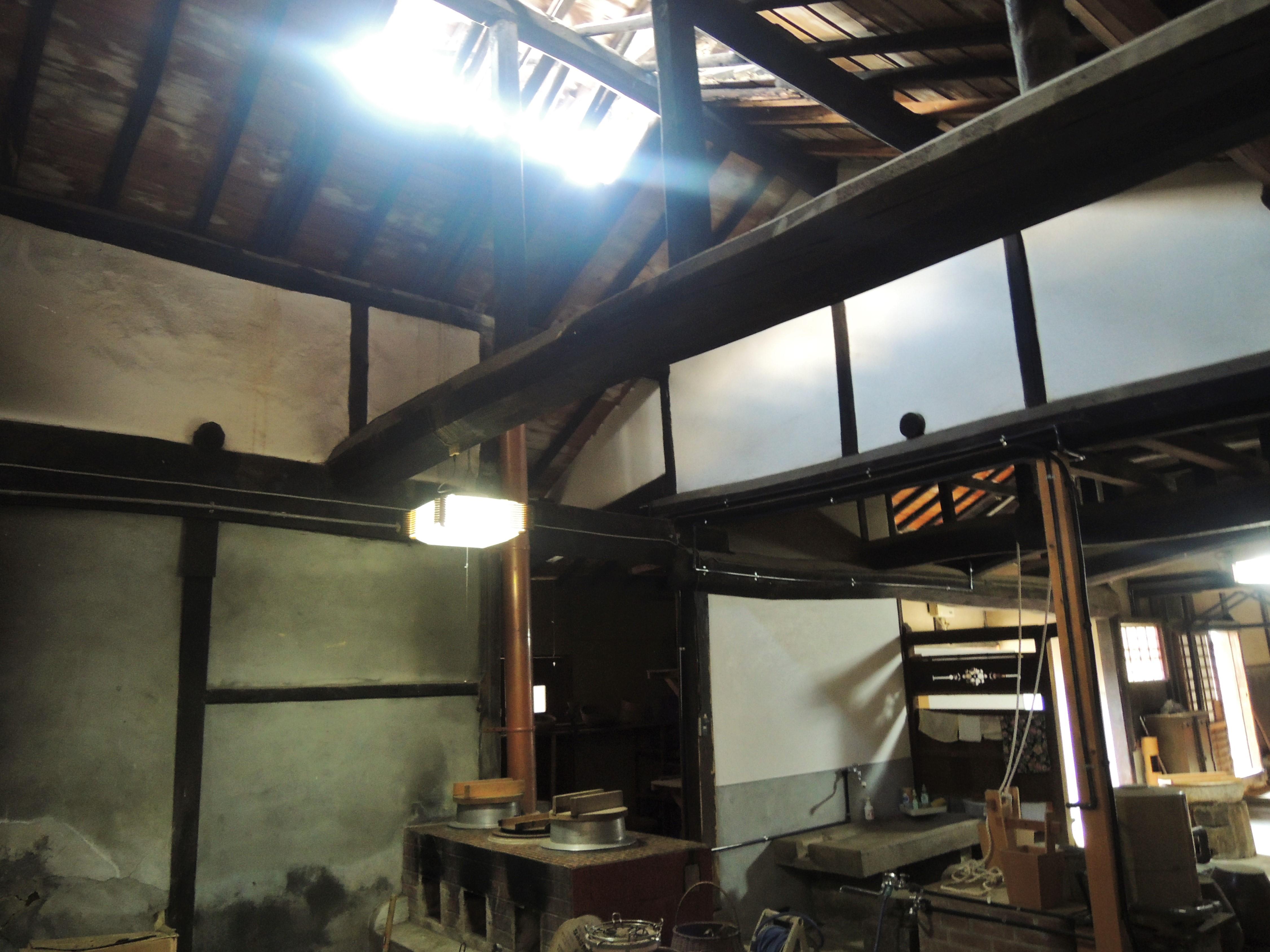 <p>煙出しのある台所棟</p>土間床で井戸・竈・流しがあり,煙出から明るい光も入る。以前は竈に7個の焚口があり大人数の食を賄った。