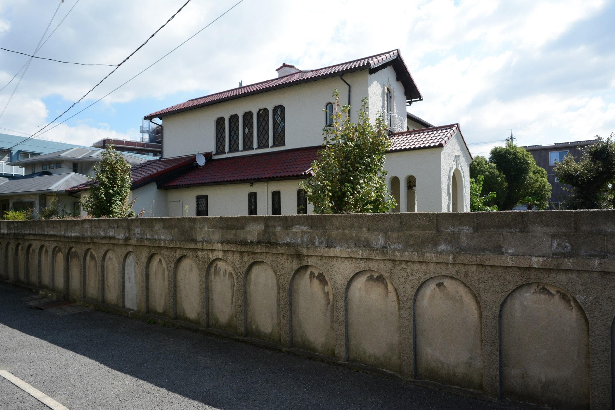 <p>敷地を囲む塀</p>塀は半円アーチを浅く彫りくぼめ、柱型を作り出している。