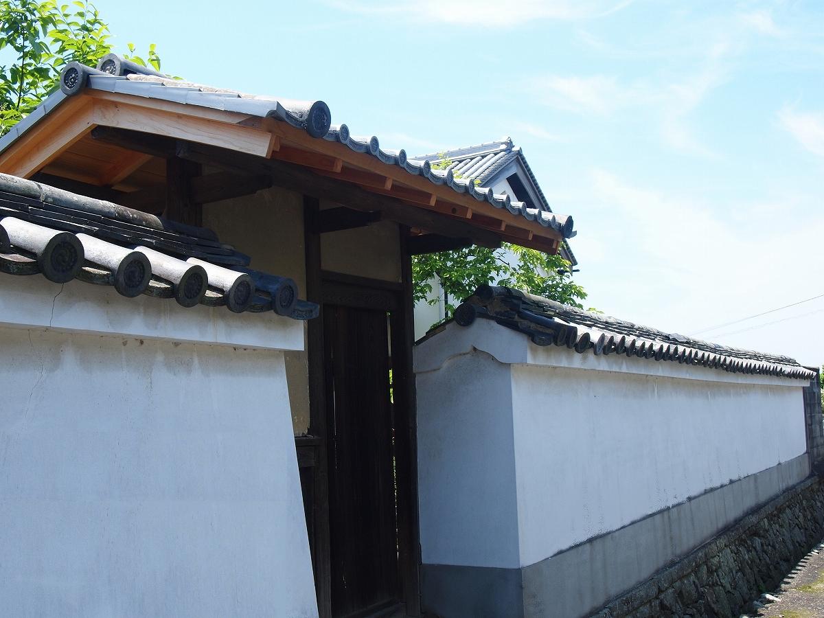 <p>敷地北側の中央の門がある土塀</p>表門両側,敷地北側と土蔵の西側に延びる版築造本瓦葺の土塀。強固な構造で道なりの高低差を石積で処理。