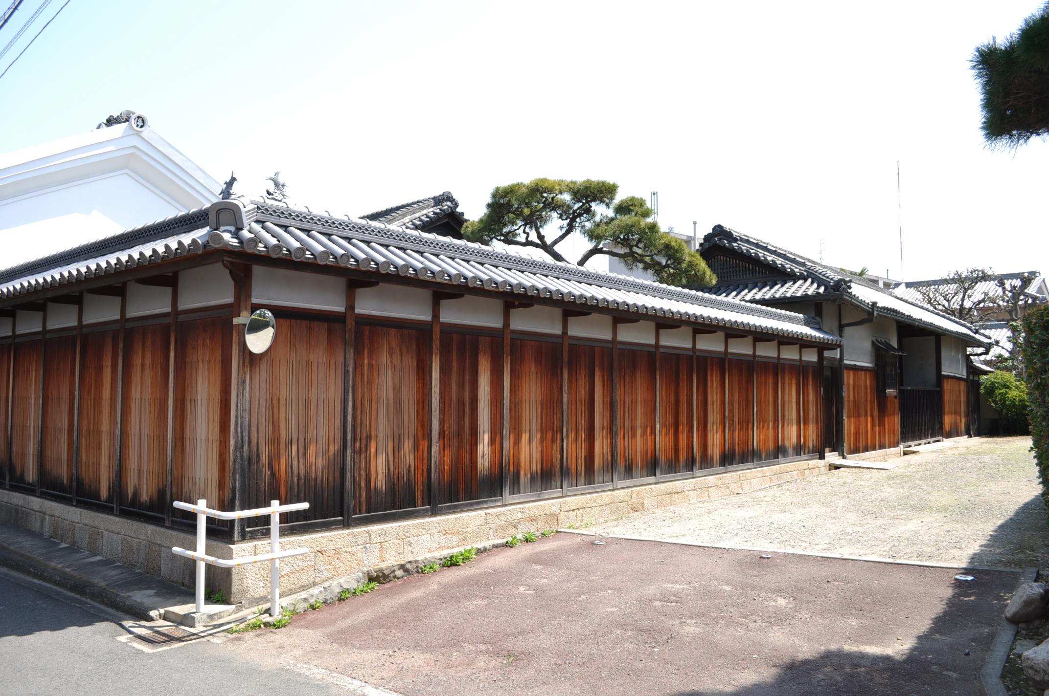 <p>地域の景観の核となる長屋門</p>中央は内開き板戸,左右は背面に戸口をもつ室とする。外壁は鼠漆喰塗と真壁造を併用し,出格子窓を設ける。