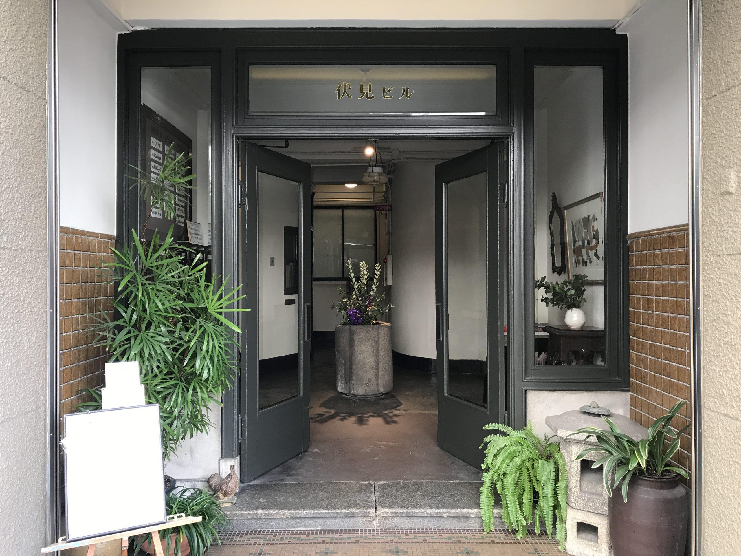 <p>正面玄関</p>木製の扉。欄間には金文字で伏見ビルと書かれている。<br /> 奥の手水鉢には常に花が活けられ、出迎えてくれる。