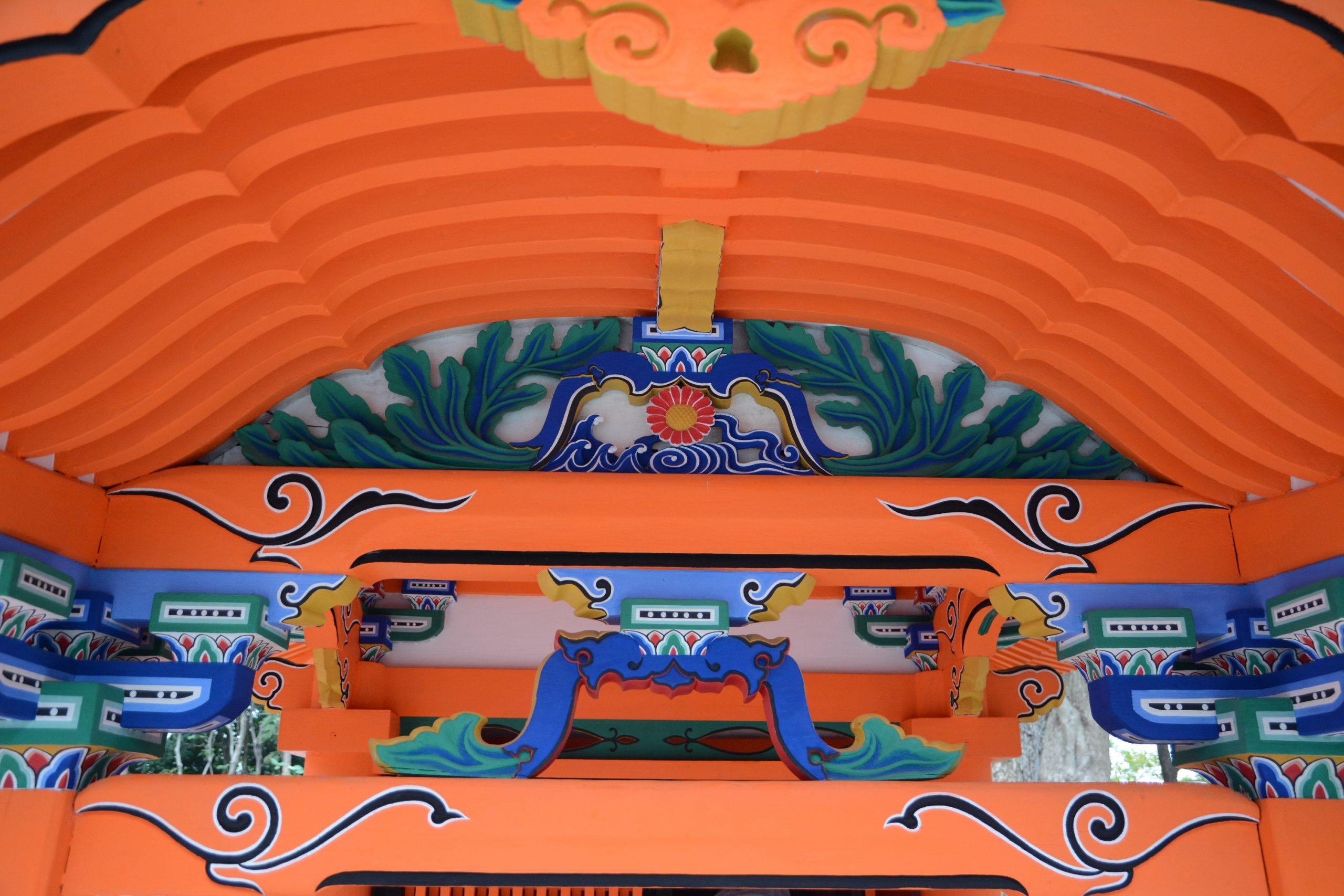 <p>向拝上部の詳細</p>向拝虹梁上の軒桁受の蟇股は、内部に菊水を飾り輪郭の足元は、長大な若葉(菊の葉)に発達している。